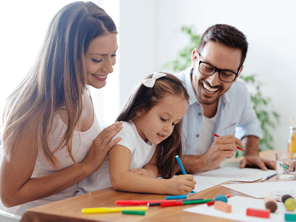 Imagen actividad 3: Niña junto a su familia coloreando en casa