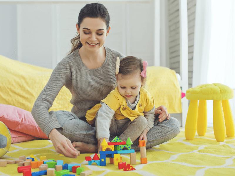 Mamá e hija jugando con cubos de madera
