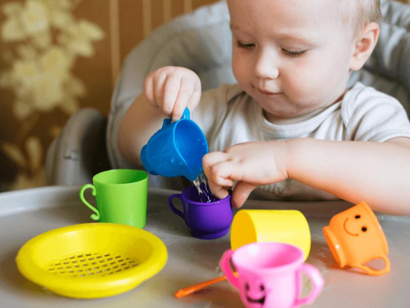 Bebé pasando agua de un lado a otro con sus juguetes