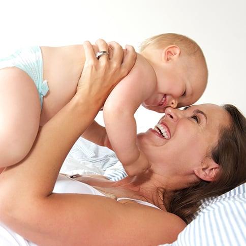 Mamá recostada cargando a su bebé