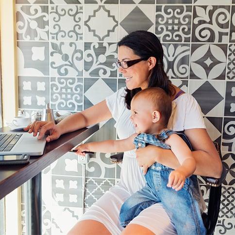 Mujer con bebé sentada frente a computadora