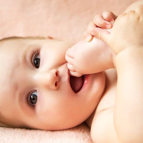 Bebé mordiendo dedo de su pie