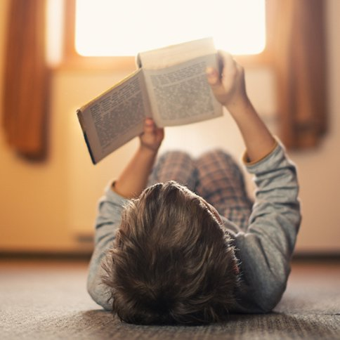 Niña leyendo acostada